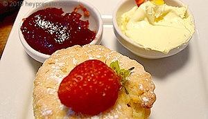 Scone topped with a fresh strawberry and small containers of strawberry jam and cream