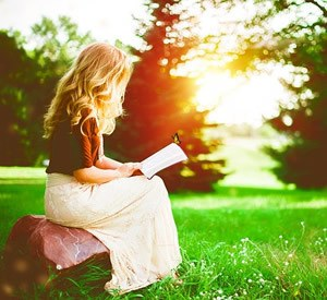Girl reading in park and sunlight