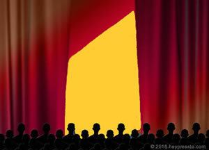 Silhouette of audience befor stage with partly open high red curtains