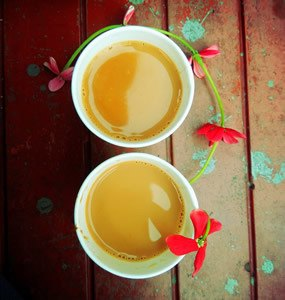 two cups of tea with red flowers on wooden table with green paint spashes