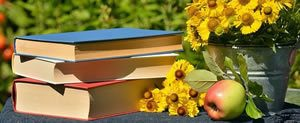 Pile of three books on table with apple and metal pot of yellow flowers