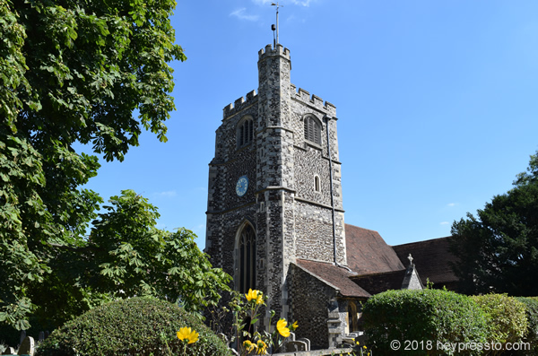 Sunken Madley - Monken Hadley church against blue sky, trees on left, yellow flowers in the foreground