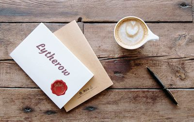 envelope coffe and pen on a table. Envelope text: Lytherow and a red seal