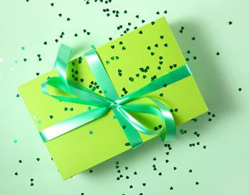 Green gift-wrapped book on green background with tiny gold hearts confetti