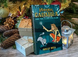 Amanda Cadabra and The Flawless Plan by Holly Bell paperback under Christmas tree next to wrapped presents 10 percent discount