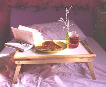 book on breakfast tray on bed with toast and tea - for new year resolutions