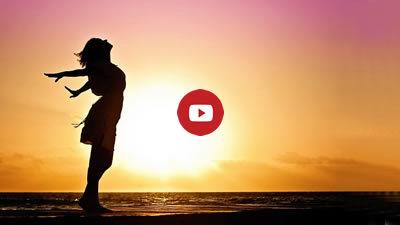 free silhouette of woman in front of sunrise seascape with Youtube play button - link to video