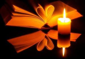 candle and book with centre pages folded into heart reflected in black surface