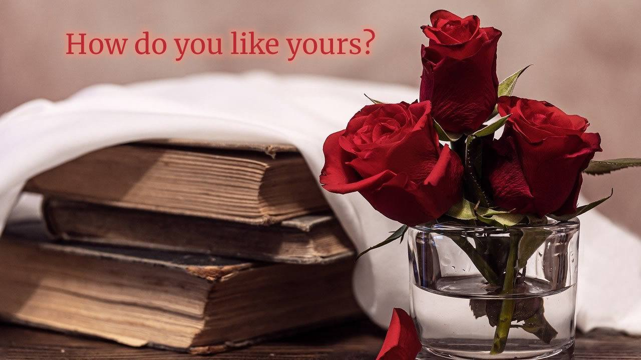 Love in Your Literature – How Do You Like It? Glass of red roses with old books beside it under a white handkerchief. Text: How do you like yours?