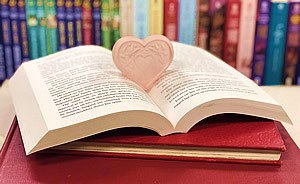 romance in literature - open book with heart in the middle and colourful books on a shelf in the background