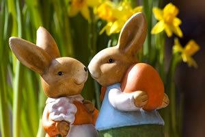 Customs: 2 ceramic Easter bunnies, one holding an orange egg with daffodils in the background