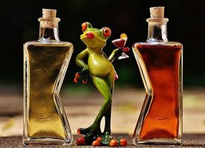 Cocktail - Ceramic frog holding cocktail glass, standing between two bottles of red and yellow liquid