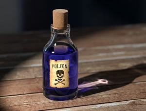Little botte of purple liquid marked poison, on wooden table in the sunshine