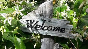 Wooden welcome sign set in a hedge with flowers