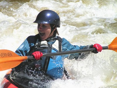 girl smiling in kayak on white water