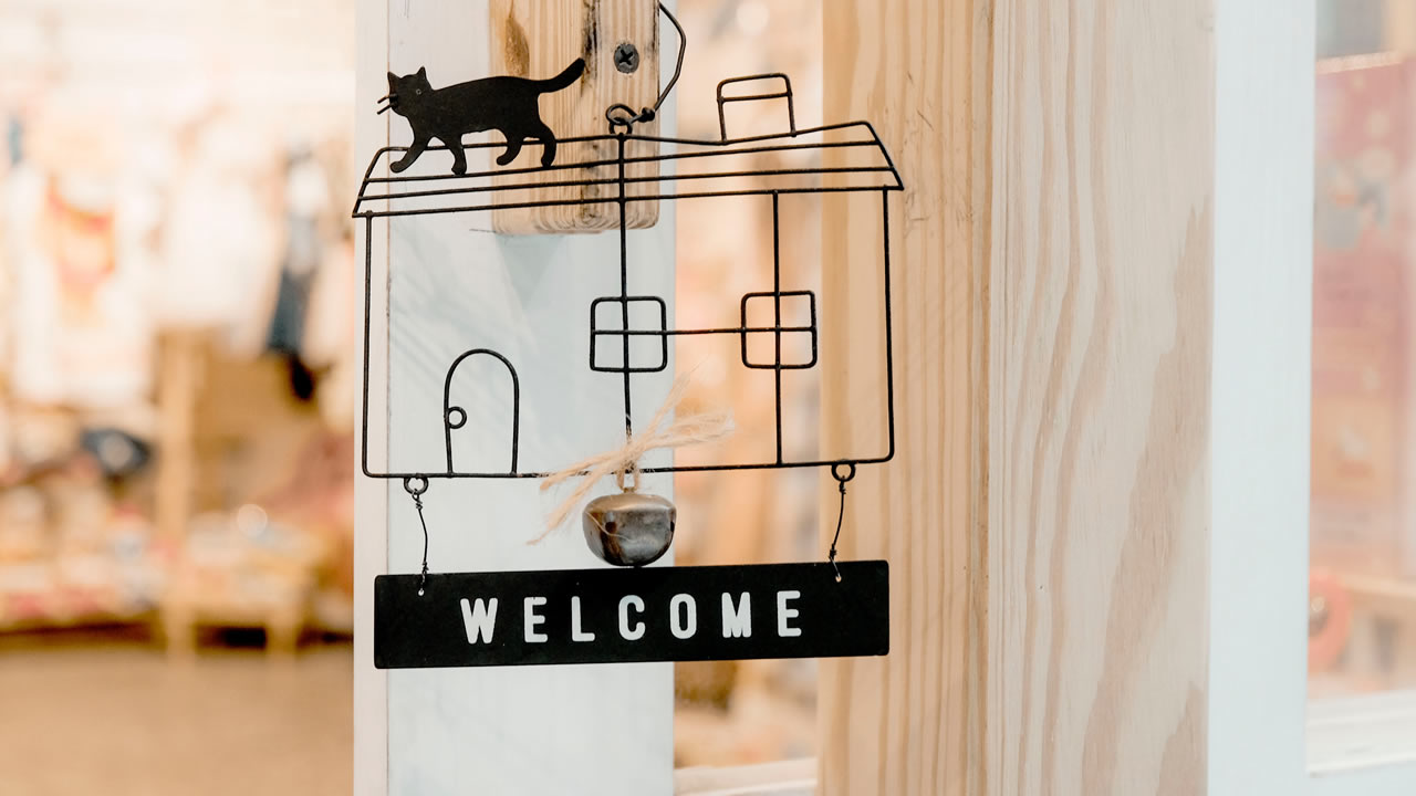 Welcome sign on an open glass door: Black wire house with cat on the roof and Welcome sign below