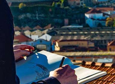 On left foreground male artists arm and hands sketching with sunny city in the background