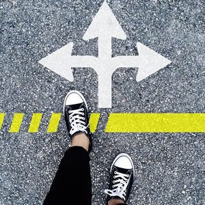 Road with three arrows pointing left, right and straight ahead. Feet standing a a yellow line, left foot forward. Trying to choose which direction