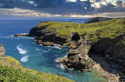 Coast of Cornwall in sunshine. Green grass and turquoise sea