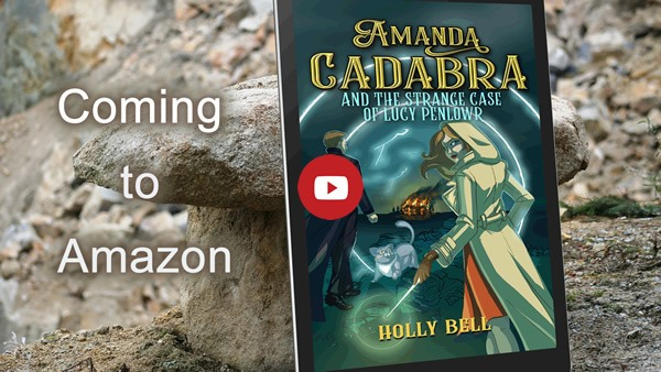 Link image to YouTube book trailer: Amanda Cadabra and The Strange Case of Lucy Penlowr by Holly Bell on ereader leaning against a granite rock. Text: Coming to Amazon