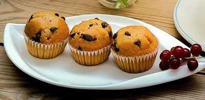 3 muffins on a leaf shaped white plate with a small bunch of berries on the right hand side
