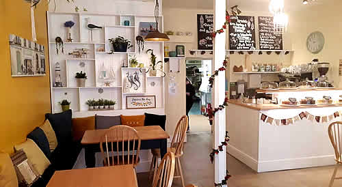 Inside the Twisted Current Cafe. White shelves with nautical artwork, wooden tables, bright interior