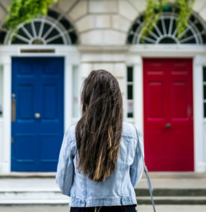 Back view of woman with a red door and a blue door in the background - which to choose?