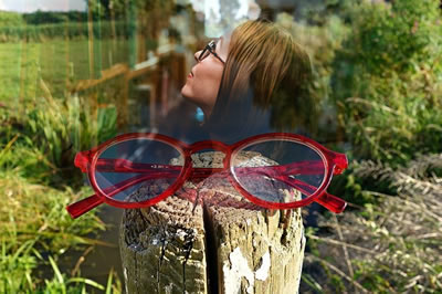 Red frames glasses on a wooden post in countryside merging into woman wearing glasses in a library