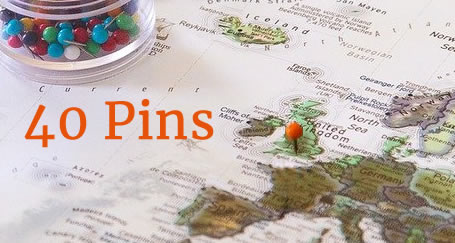 Container of map pins on a map of Europe with an orange pin in London